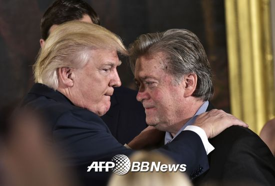US President Donald Trump (L) congratulates Senior Counselor to the President Stephen Bannon during the swearing-in of senior staff in the East Room of the White House on January 22, 2017 in Washington, DC. / AFP PHOTO / MANDEL NGAN
